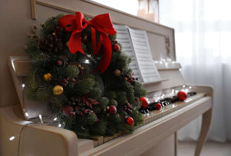 White piano with decorative wreath indoors, closeup. Christmas music