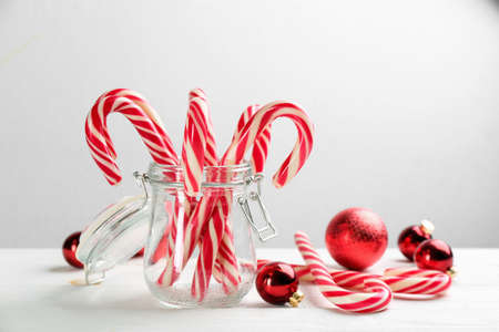 Many sweet candy canes and Christmas decor on white wooden table. Space for text Stock Photo
