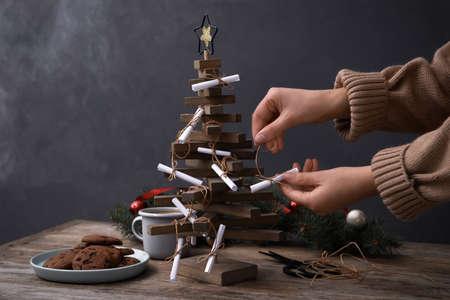 Woman making advent calendar at wooden table, closeup