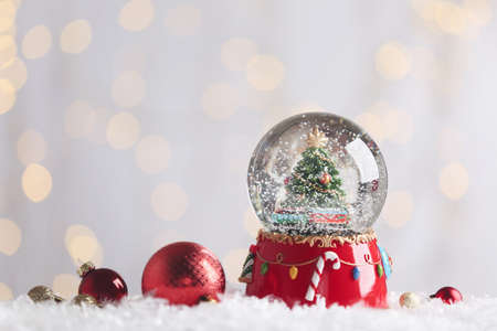 Beautiful snow globe and baubles against blurred Christmas lights. Space for text