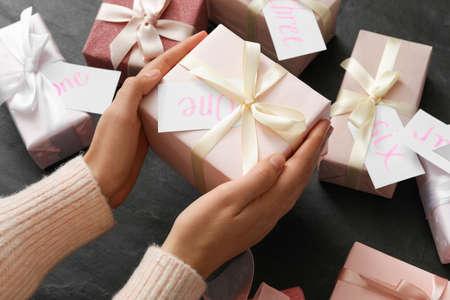 Woman with gift box at black table, closeup. Advent calendar 免版税图像