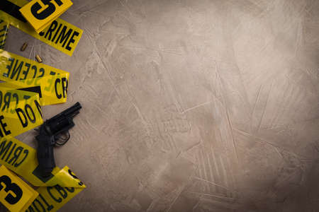 Flat lay with yellow tape, crime scene marker and gun on gray stone background. Space for text