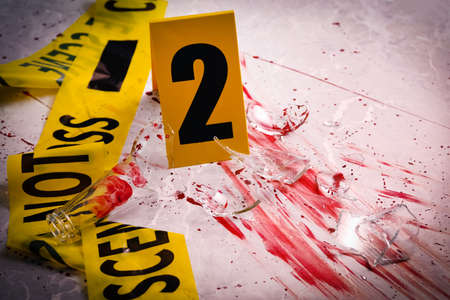Yellow tape, crime scene marker and smithereens in blood on marble table, closeup