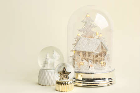 Different beautiful snow globes on beige background