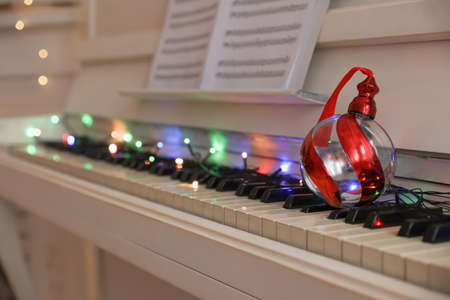 Beautiful bauble on piano keys indoors, space for text. Christmas music Stock Photo