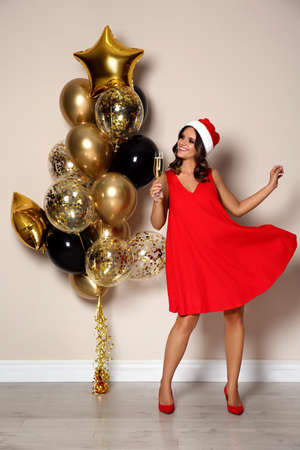 Happy woman in Santa hat with champagne and air balloons near beige wall indoors. Christmas party