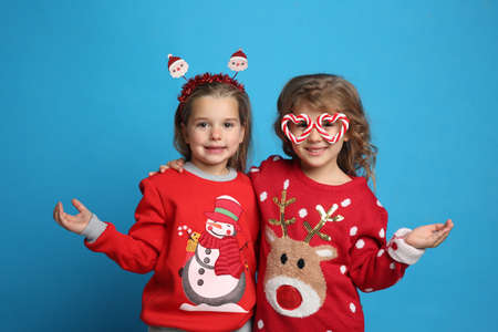 Kids in Christmas sweaters and festive accessories on blue background 版權商用圖片
