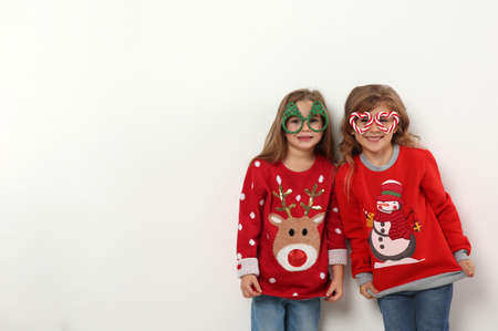 Kids in Christmas sweaters and festive glasses on white background