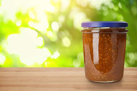 Jar of fig jam on wooden table against blurred background, space for text