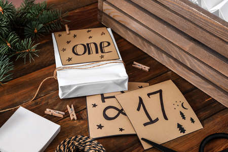 Composition with gift bag and paper notes on wooden table, closeup. Creating advent calendar 免版税图像
