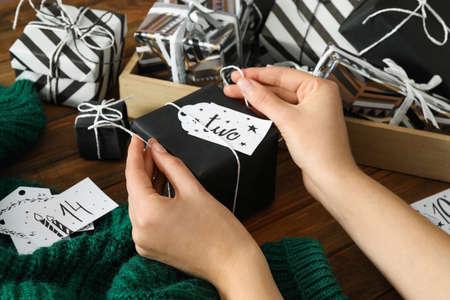 Woman decorating gift box at wooden table, closeup. Creating advent calendar