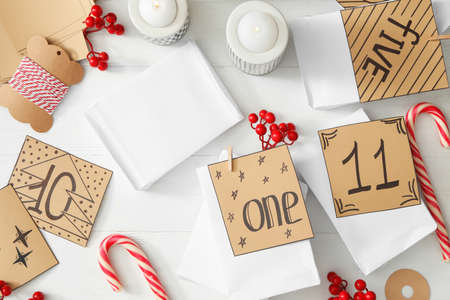 Flat lay composition with gift bags on white wooden table. Creating advent calendar