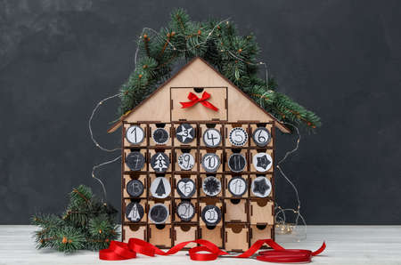 House shaped advent calendar with garland and fir tree on white wooden table against dark background 免版税图像