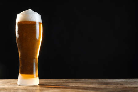 Cold tasty beer on wooden table against dark background. Space for text