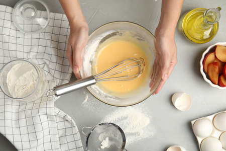 Woman with dough and ingredients for cake at light gray table, top view Фото со стока