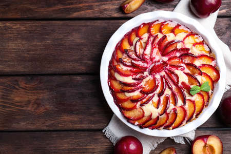 Delicious cake with plums on wooden table, flat lay. Space for text Reklamní fotografie
