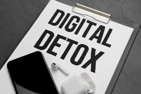 Clipboard with phrase DIGITAL DETOX, smartphone and earphones on black stone table, closeup