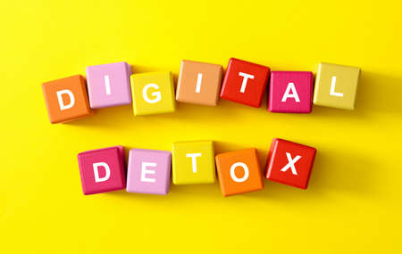Colorful cubes with phrase DIGITAL DETOX on yellow background, flat lay