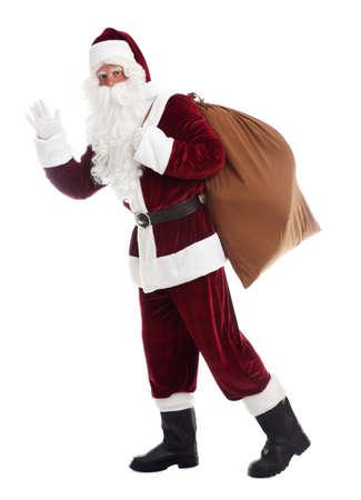 Santa Claus with sack walking on white background Stock Photo