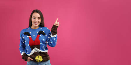 Young woman in Christmas sweater on pink background, space for text
