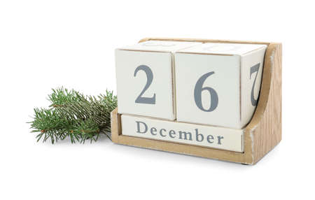 Wooden block calendar with date 26th of December near fir tree branch on white background. Boxing day 免版税图像