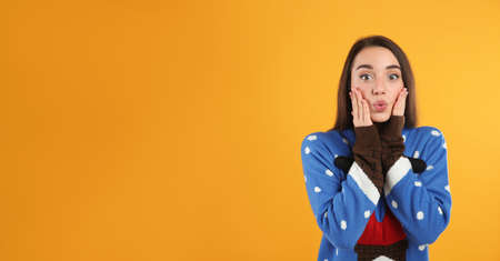 Surprised young woman in Christmas sweater on yellow background, space for text