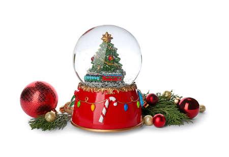 Beautiful snow globe, Christmas balls and coniferous twigs on white background