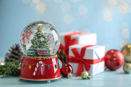 Beautiful snow globe with Christmas tree, gifts and decor on light blue table Stock Photo