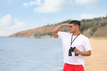 Handsome male lifeguard with binocular near sea