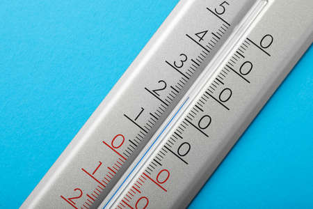 Weather thermometer on light blue background, closeup