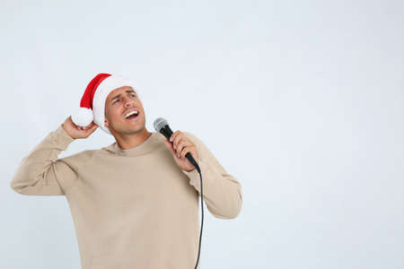Emotional man in Santa Claus hat singing with microphone on white background, space for text. Christmas music Stock Photo