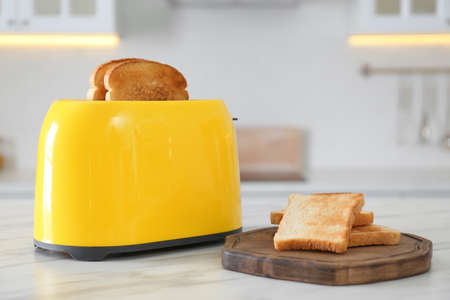 Modern toaster and bread slices on white marble table in kitchen