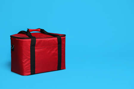 Modern red thermo bag on light blue background. Space for text