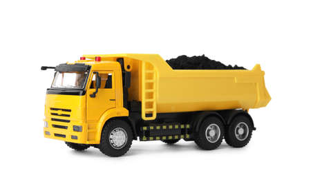 Yellow toy tipper truck with coal isolated on white