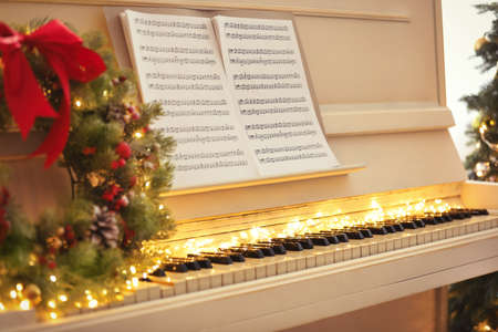 White piano with fairy lights and note sheets indoors, closeup. Christmas music Stock Photo