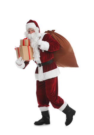Santa Claus with sack and gifts walking on white background