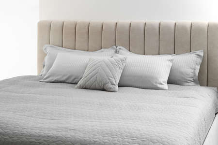 Many soft pillows on large comfortable bed indoors