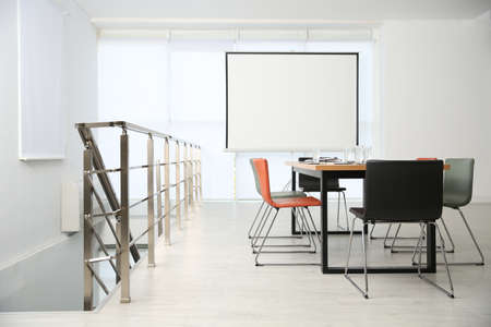 Modern meeting room interior with large table and projection screen