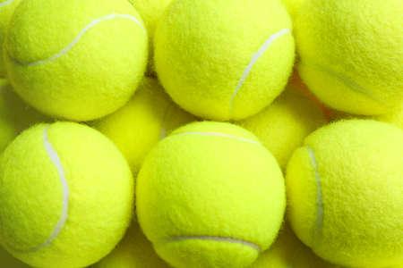 Tennis balls as background, closeup. Sports equipment