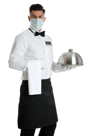 Waiter in medical face mask holding tray with lid on white background