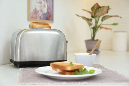 Modern toaster with slices of bread on white table in kitchen