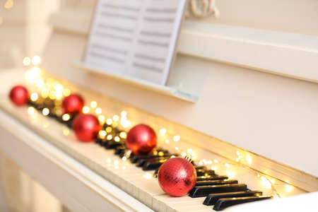 Red baubles and fairy lights on piano keys, closeup. Christmas music