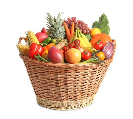 Basket with assortment of fresh organic fruits and vegetables on white background