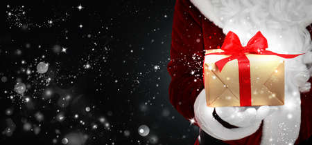 Santa Claus holding gift box on black background with snowflakes, bokeh effect. Space for text