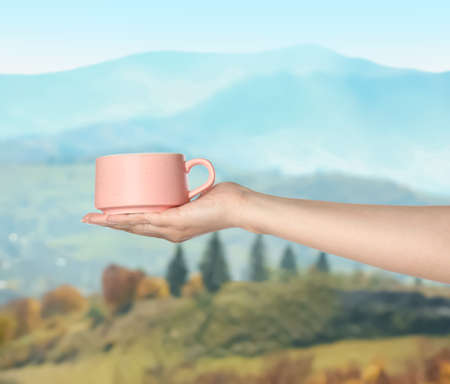 Closeness to nature. Woman holding cup in mountains, closeup