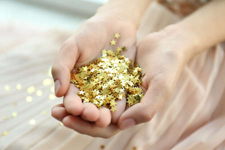 Woman holding confetti stars, closeup. Christmas celebration