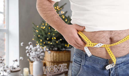 Overweight man measuring his waist in room decorated for Christmas after holidays, closeup