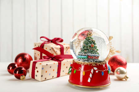 Beautiful snow globe, gift boxes and Christmas balls on white wooden table