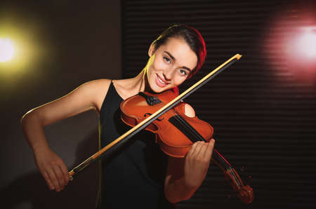 Beautiful young woman playing violin in dark room Reklamní fotografie