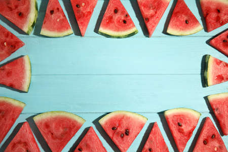 Frame made with slices of ripe watermelon on light blue wooden table, flat lay. Space for text Stock fotó